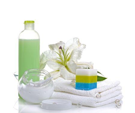 lirio blanco: lirio blanco, toallas, velas, crema de cuerpo en el fondo blanco