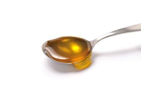 cucchiaio di miele su sfondo bianco