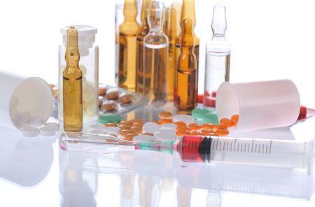 colorful pills, ampules, syringle on white background photo