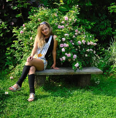 rosebush: young and beautiful blond girl in summer garden near blooming rosebush Stock Photo