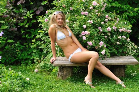 young and beautiful blond girl in summer garden near blooming rosebush photo