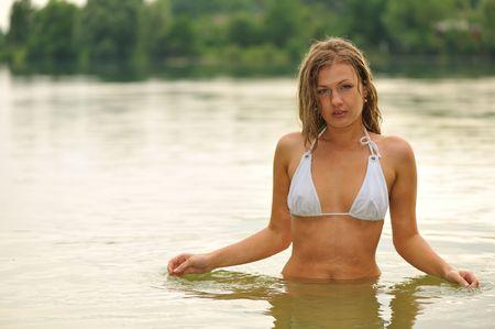 wet attractive blond girl enjoying in water in summer twilight