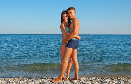 young attractive couple on summer beach against blue sea photo