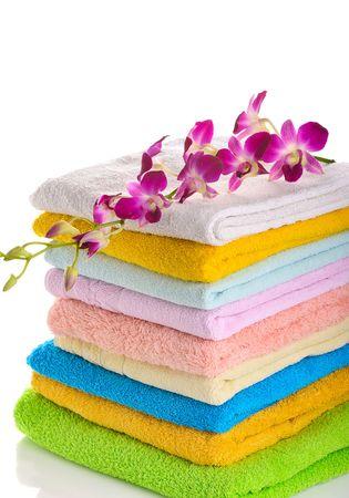 pila di asciugamani colorati con rosa orchidea isolata on white background