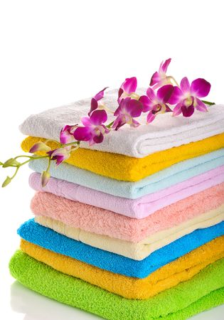 downy: stack of colorful towels with pink orchid isolated on white background