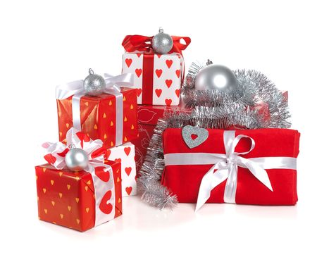 heap of Christmas red gifts decorated with silver balls and tinsel on white background