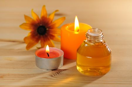 traquility: burn scented candles  with brown bottle with essential oil on wood background