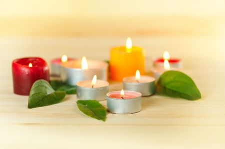 traquility: colorful burn scented candles  with green leaves  on wood background