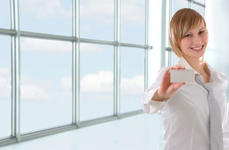 cheerful young girl holding business card in office interior (focus on card) photo