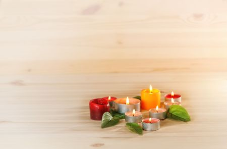 traquility: burn scented candles  and green leaves on wood background  with copyspace