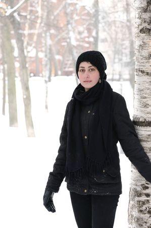 very beautiful girl standing near birch tree in winter park  photo
