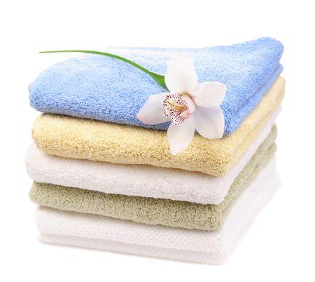 pila di asciugamani colorati con orchidea bianca isolato su sfondo bianco  Archivio Fotografico