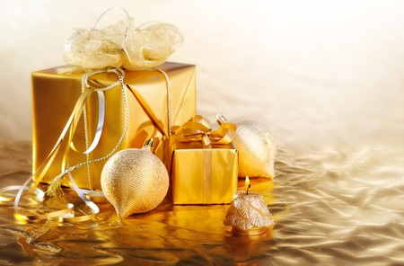 golden Christmas gifts,balls, candle on gold shine background Stock Photo