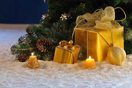 golden Christmas gift boxes with burn candles under decorated fir on snow photo