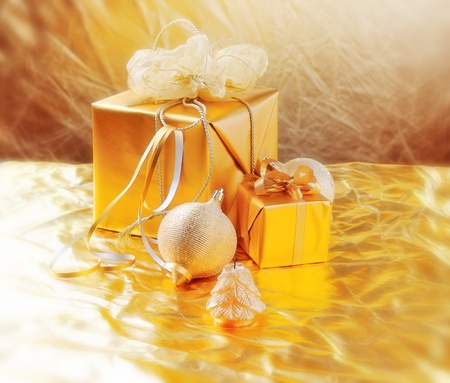 adorn: golden Christmas gifts,balls, candle on gold shine background Stock Photo