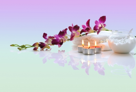 white towels,pink orchid, burn candles, body cream  with reflections    Stock Photo