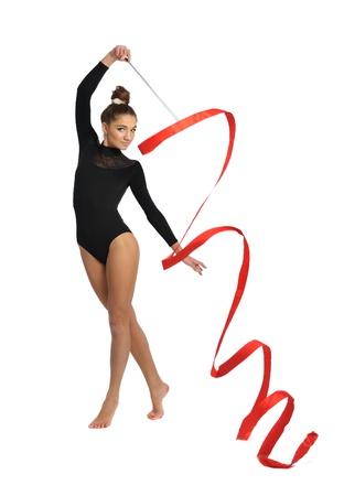 rhythmic gymnastic: chica gimnasta con traje negro de deporte con cinta roja aislado en fondo blanco Foto de archivo