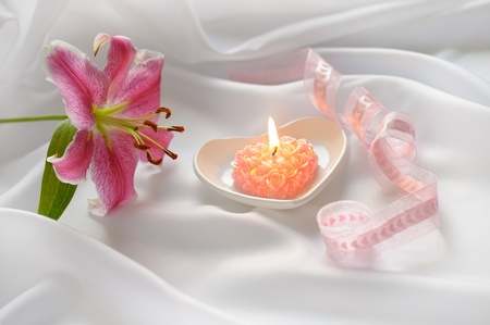 pink roses heart-shaped candle with pink lily on white silk background   photo