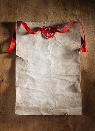 foglio del vecchio libro sulla superficie del legno con nastro rosso e cuore