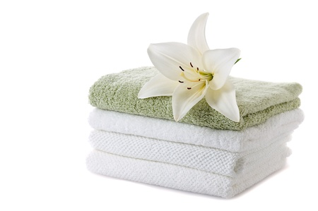 stack of towels with white lily isolated on white background photo