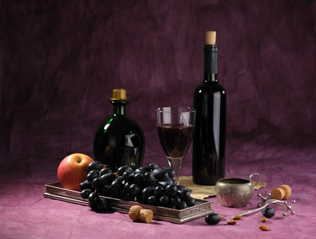 still life with bottle of red vine and black grape on dark background photo