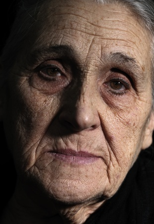 grizzled: low key portrait of old woman close- up Stock Photo