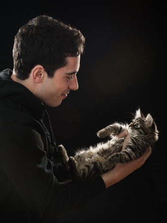 young  handsome man holding little kitten on dark background photo