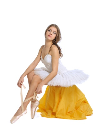 ballerina tying her ballet slippers on white background photo