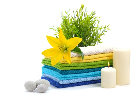 stack of colorful towels with yellow lily and burn candles isolated on white background photo
