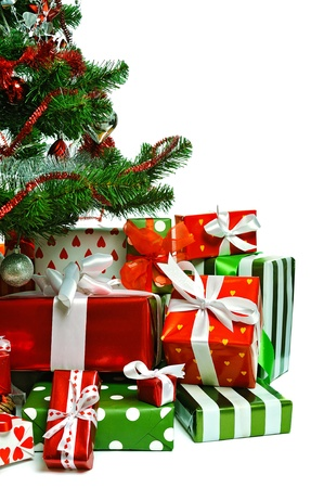 Christmas tree with heap of red gift boxes decorated with satin ribbon isolated on white background Stock Photo