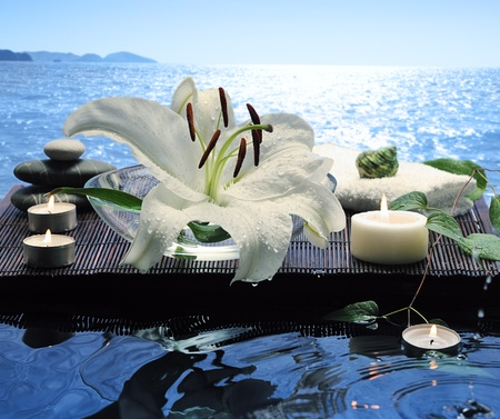 sea spa with white lily and floating burn candles
