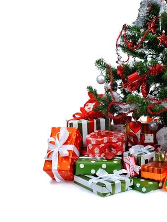 Albero di Natale con heap di confezioni regalo festivo decorato con nastro di raso isolato su sfondo bianco