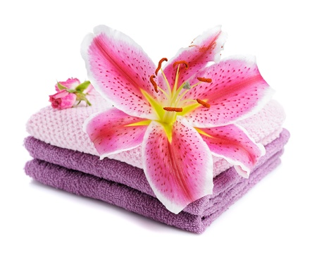 stacked towels with pink lily  isolated on white photo