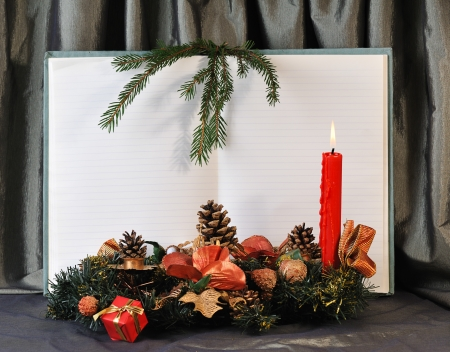 blank pages of old open notebook bordering with christmas decoration and red burn candle photo