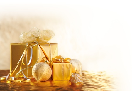 gold  Christmas gifts with balls and candle on gold background photo