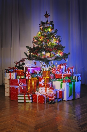 heap of  gift boxes   under decorated Christmas tree in dark room photo