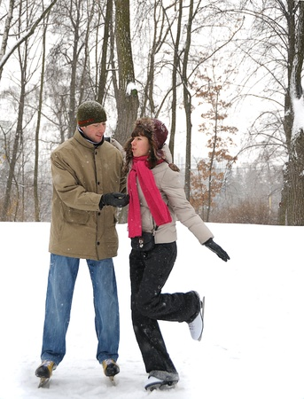 young couple in winter skate rink photo