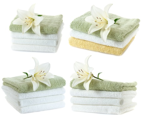 absorb: stack of towels with white lily isolated on white background