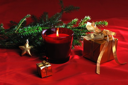 red burn candle with christmas decoration on red background photo