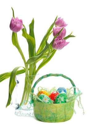 colorful easter eggs in basket and pink tulips in glass on white background photo