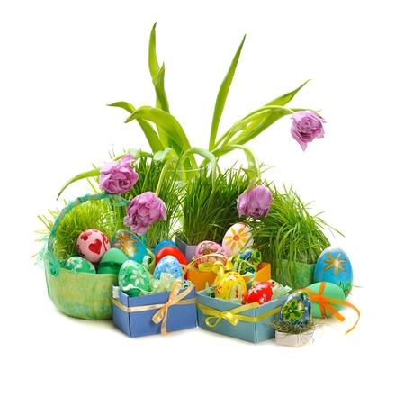uova di Pasqua decorate con tulipani e l'erba verde su sfondo bianco Archivio Fotografico
