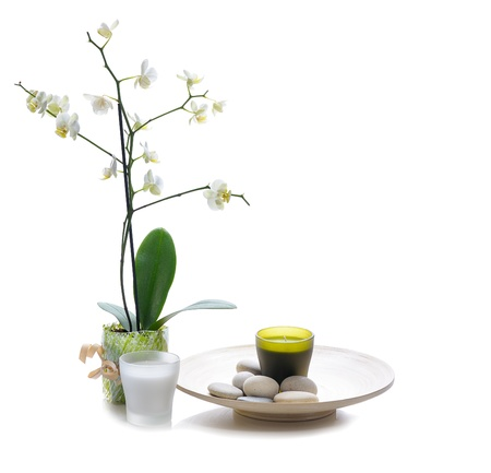 white orchid with candle and massage stones on platter, isolated on white photo