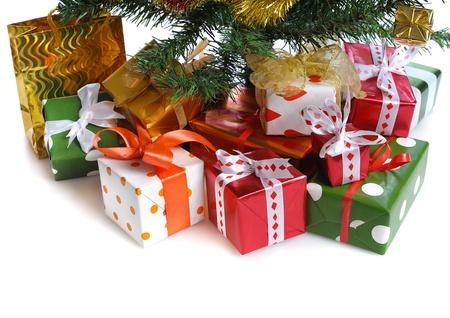 ornated: mucchio di scatole regalo rosso decorato con fiocco di raso sotto albero di Natale decorato