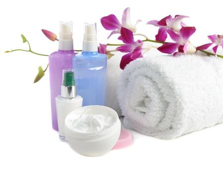 aseo personal: moisrurizer facial de cerca y flor de la orquídea en el fondo blanco Foto de archivo