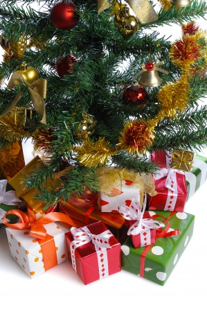 toygift:  heap of  gift boxes  ornated with satin bow  under decorated Christmas tree