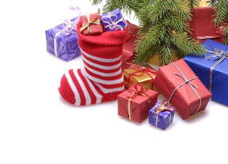 toygift: santa stocking  and  gift boxes  under decorated Christmas tree isolated on white background
