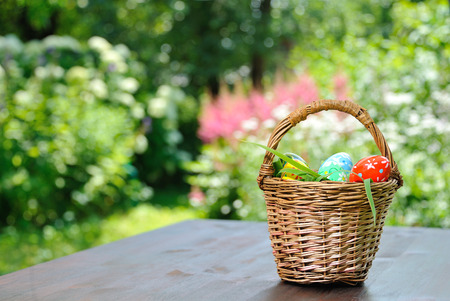basket with painted eggs standing on garden table photo
