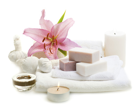 isolated on white: bars of herbal spa soap with white towels,candles and flower