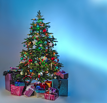 christmas isolated: decorated Christmas tree with gifts on blue background Stock Photo