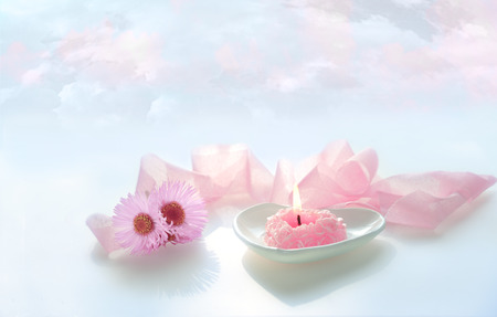 heart burn: pink heart shaped burn candle with pink ribbon and flowers on blue sky background Stock Photo